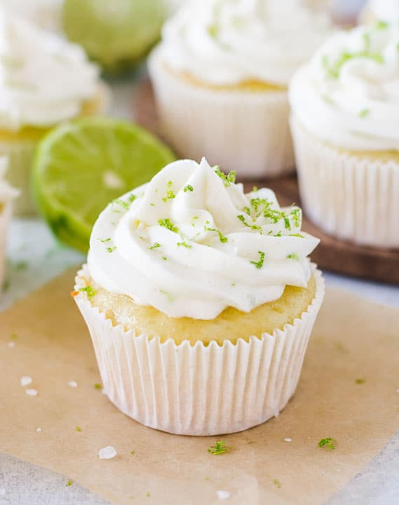 margarita cupcake sitting on a piece of parchment paper with more cupcakes in the background