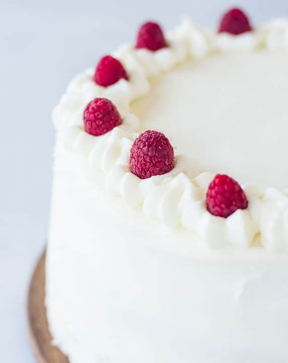 top of the frosted white chocolate raspberry cake with raspberries as garnish