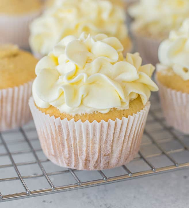 lemon curd cupcakes on a wire baking rack and topped with frosting