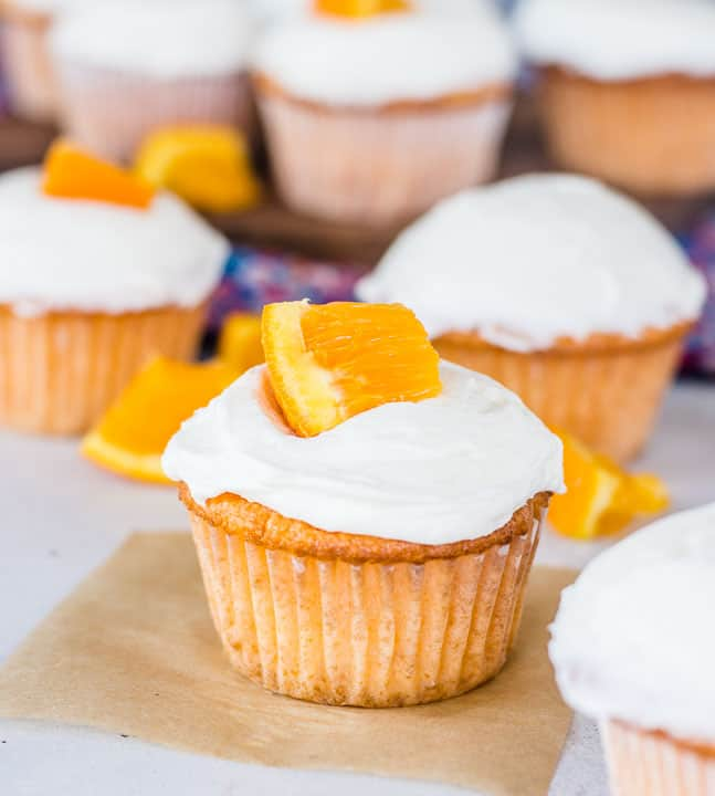 orange cupcakes topped with frosting with orange slices on top