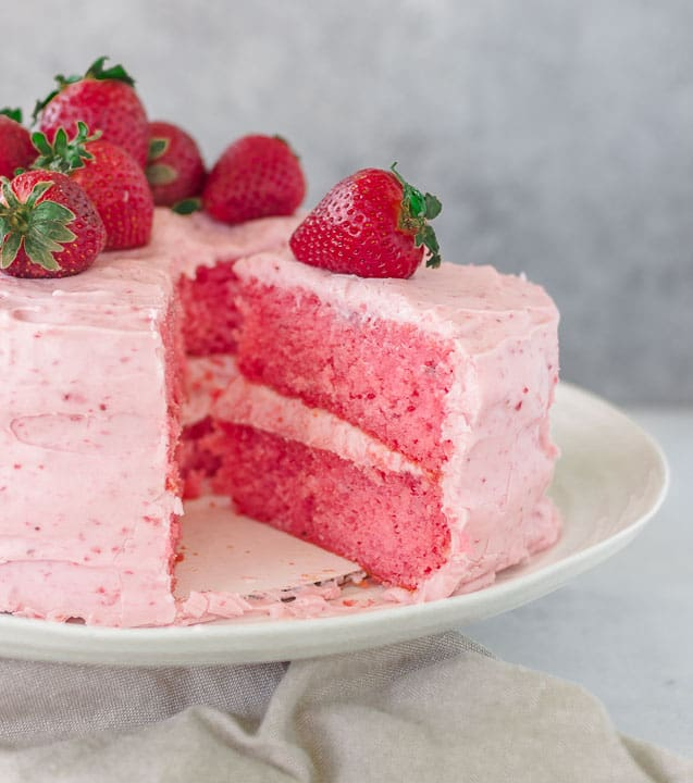 strawberry layer cake on a cake stand with a slice taken out of it