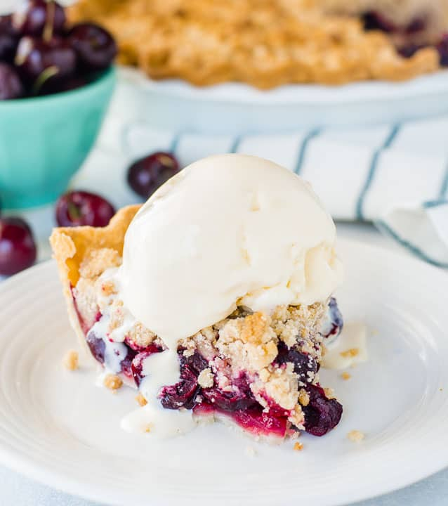 slice of cherry crumb pie on a plate with a scoop of ice cream on top
