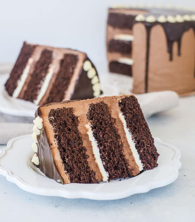 slice of tuxedo cake on a plate with the rest of the cake in the background