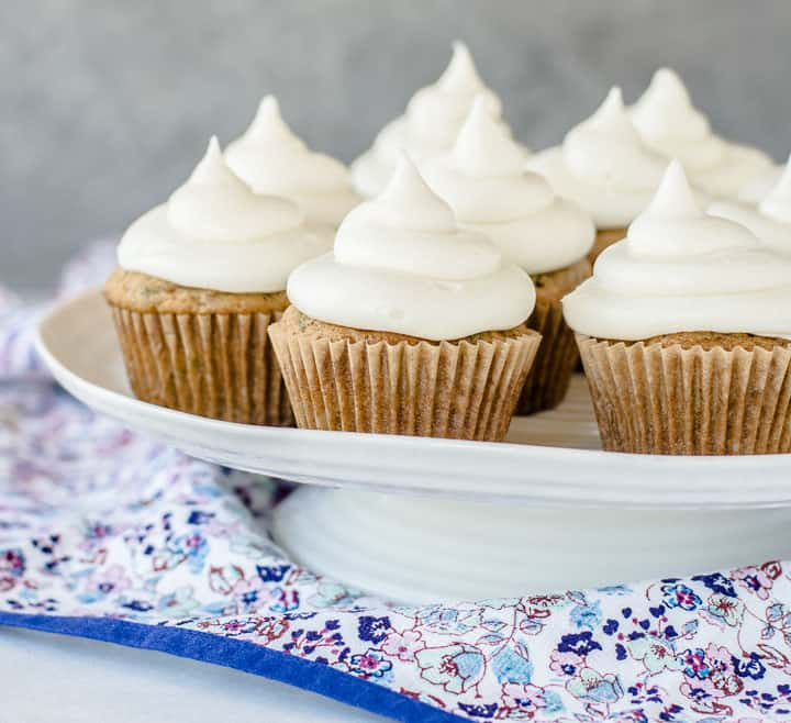 zucchini cupcakes with cream cheese frosting on a cake stand
