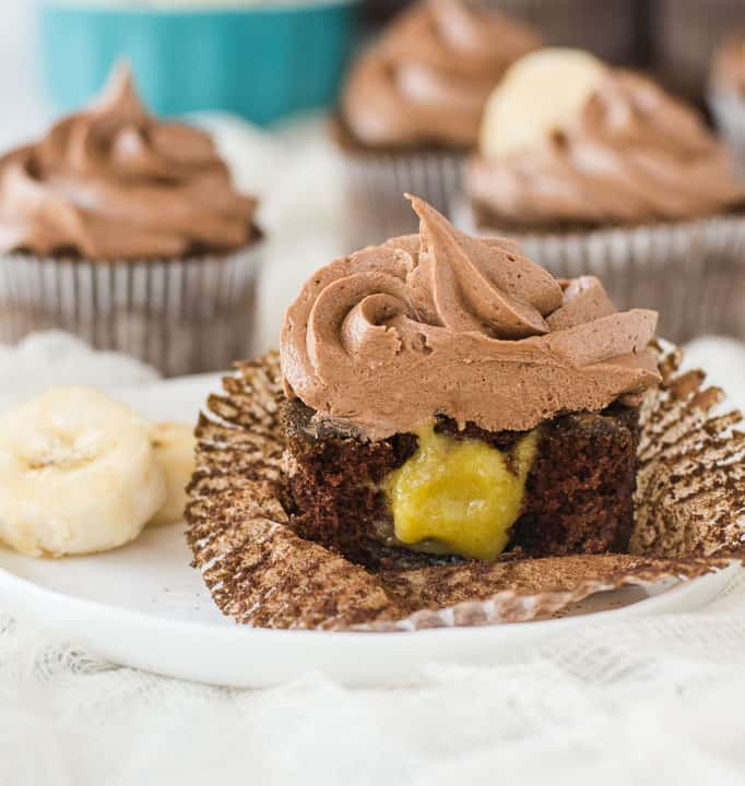 cupcake on a plate sliced in half to show the filling with more chocolate banana cupcakes in the background