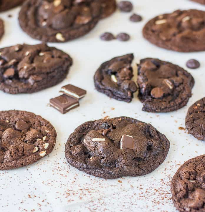 cookies scattered on a piece of parchment paper with Andes mints and chocolate chips