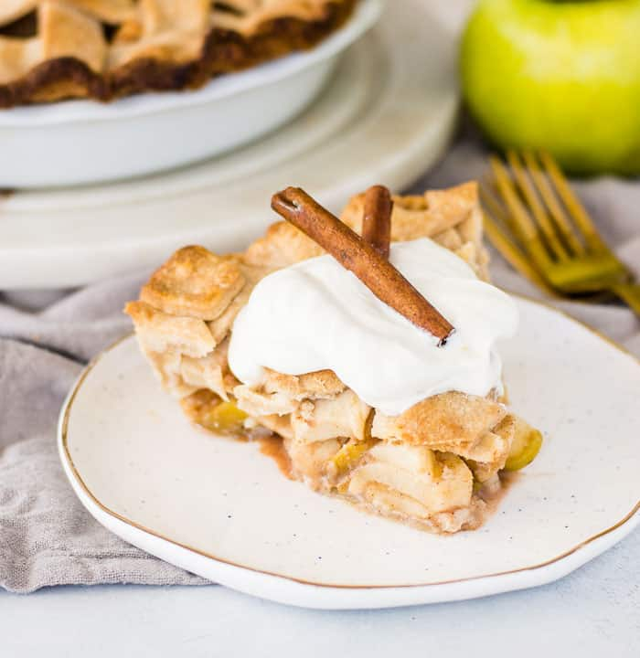 slice of cinnamon apple pie on a plate with the rest of the pie in the background