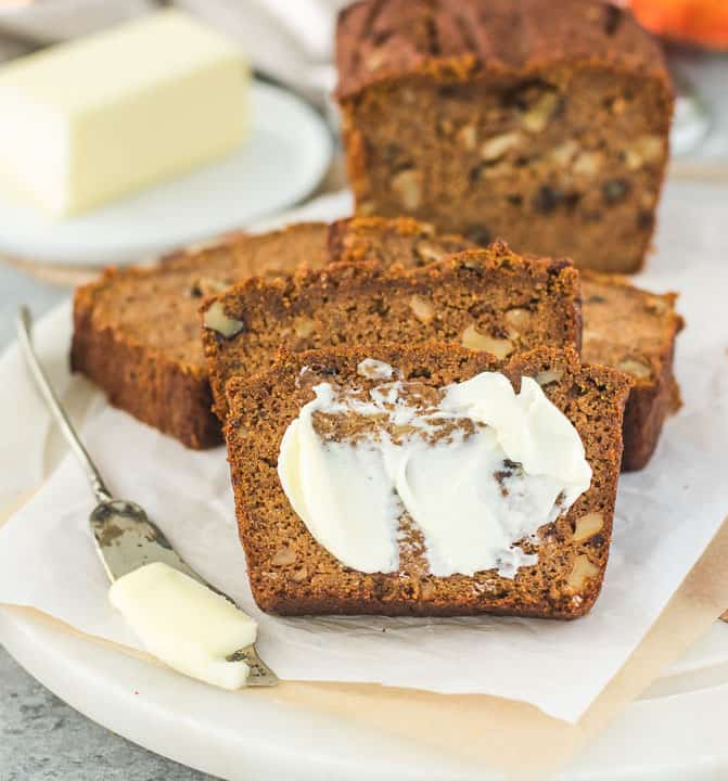 slice of paleo pumpkin bread spread with butter and more bread slices behind it