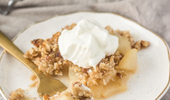 pear crisp on a plate and topped with whipped cream