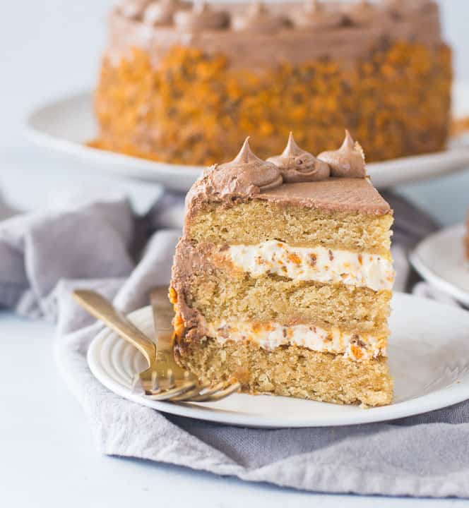 slice of butterfinger cake on a plate next to two forks with the rest of the cake in the background