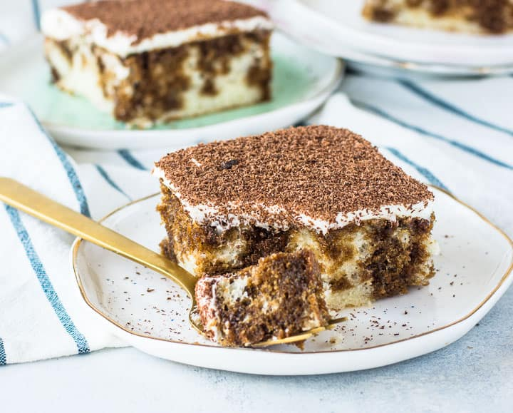 slice of easy tiramisu on a plate with a fork taking a bite out of it