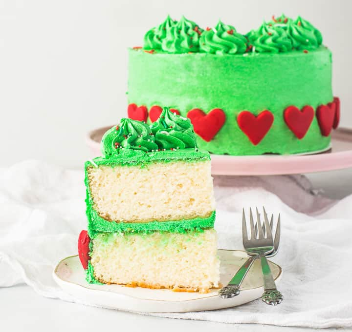 slice of grinch cake on a plate with forks next to it and the rest of the cake in the background