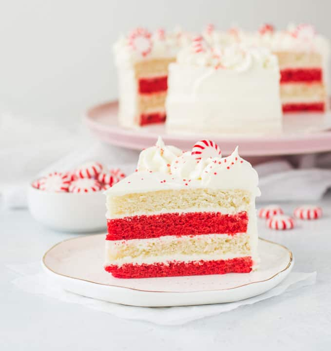 slice of peppermint cake on a plate with the rest of the cake in the background