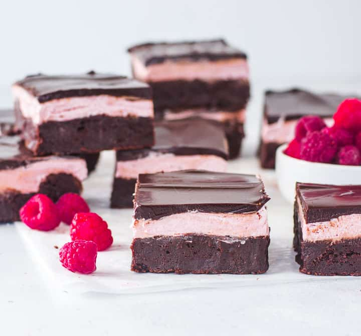 raspberry brownies on a piece of parchment paper with more brownies in the background