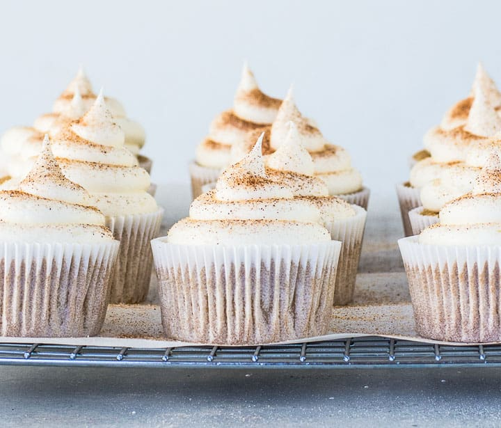 frosted snickerdoodle cupcakes on a wire cooling rack