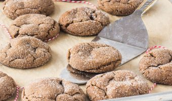 molasses ginger cookies on a baking sheet with a spatula under one of them