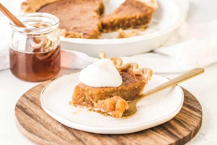 slice of honey pie on a plate with a fork taking a bite out of it