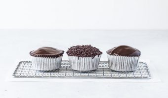three chocolate ganache cupcakes on a wire rack