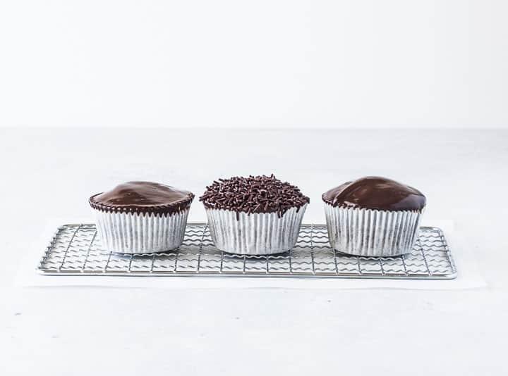 three chocolate ganache cupcakes on a wire rack