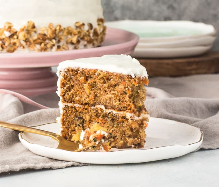 slice of carrot pineapple cake with cream cheese frosting on a plate with a fork taking a bite out of it