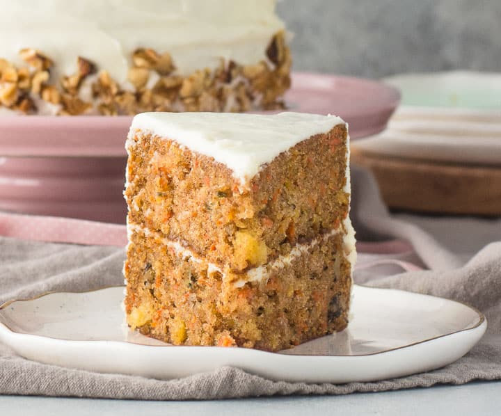 slice of carrot pineapple cake on a plate with the rest of the cake in the background
