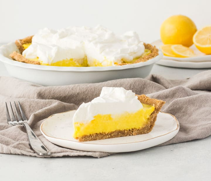 slice of lemon cream pie on a plate with the rest of the pie in the background