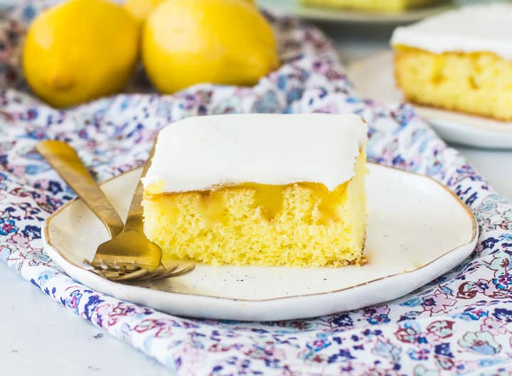 slice of lemon poke cake on a plate with lemons in the background