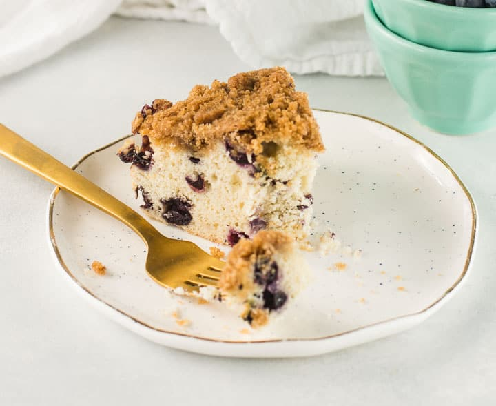 slice of blueberry buckle on a plate with a fork taking a bite out of it