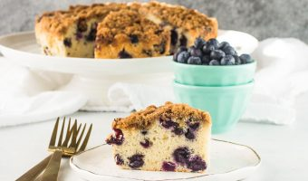slice of blueberry buckle on a plate with the rest of the cake in the background on a stand