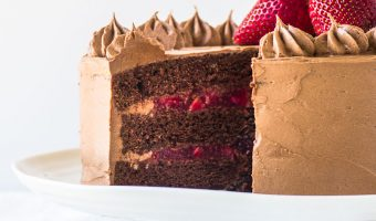 chocolate strawberry cake on a cake stand with a slice taken out of it