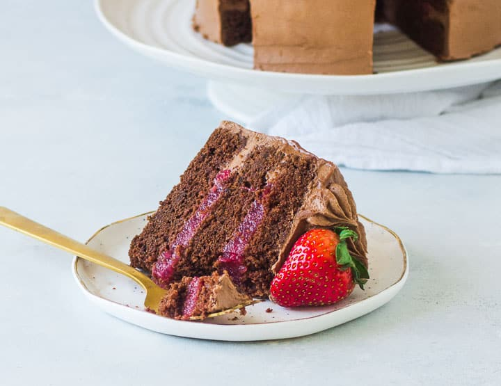 slice of strawberry chocolate cake on a plate with a fork taking a bite out of it