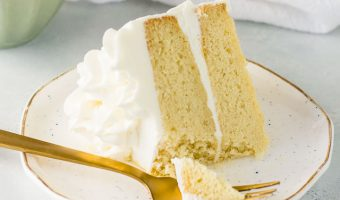slice of white chocolate cake on a plate with a fork taking a bite out of it