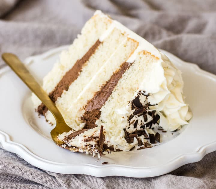 slice of black and white cake on a plate with a fork taking a bite out of it