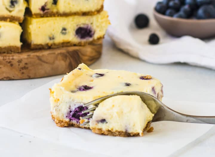 blueberry cheesecake bar on a piece of parchment with a fork taking a bite out of it