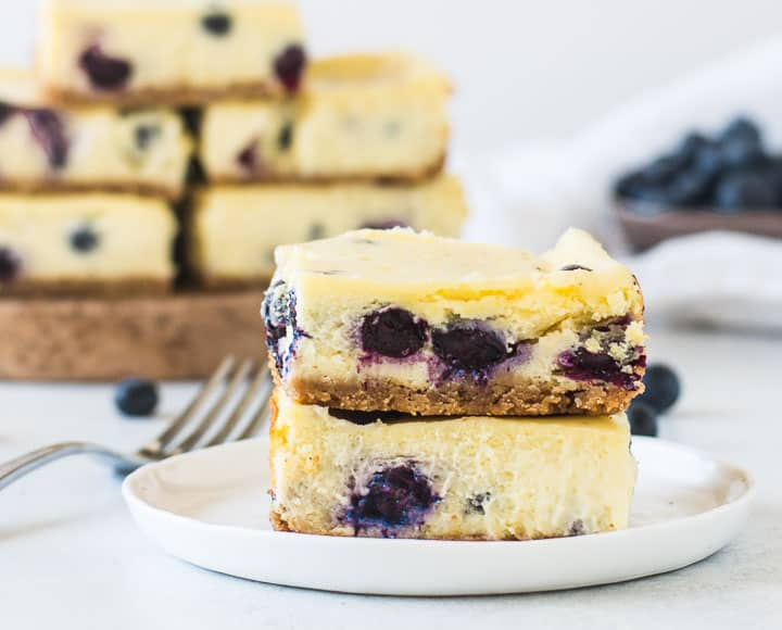 two blueberry cheesecake bars stacked on a plate with more bars in the background