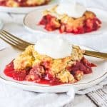 slice of rhubarb dump cake on a plate with more slices behind it