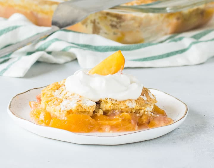 fresh peach dump cake topped with whipped cream on a plate