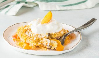 fresh peach dump cake on a plate with a fork taking a bite out of it and the rest of the cake in the background