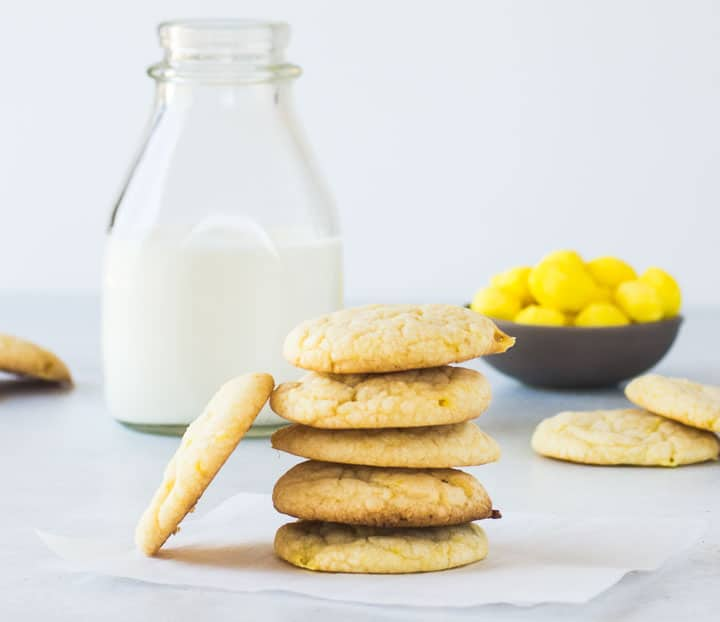 stack of lemon drop cookies in front of a bottle of milk