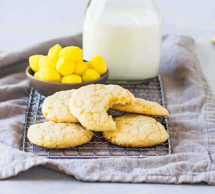 lemon drop cookies on a wire rack in front of a dish of lemon drops and a bottle of milk