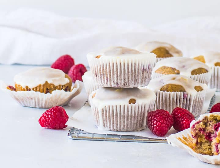 two raspberry lemon muffins stacked on a wire rack with more muffins behind them