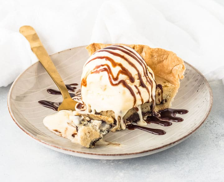 slice of chocolate chip cookie pie on a plate with a fork taking a bite out of it