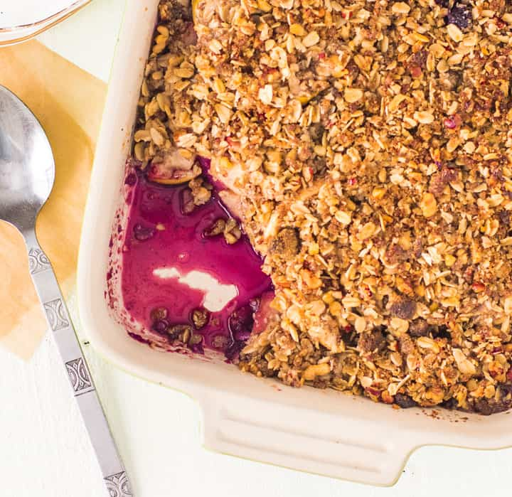 overhead photo of apple blueberry crisp in a pan with a scoop taken out