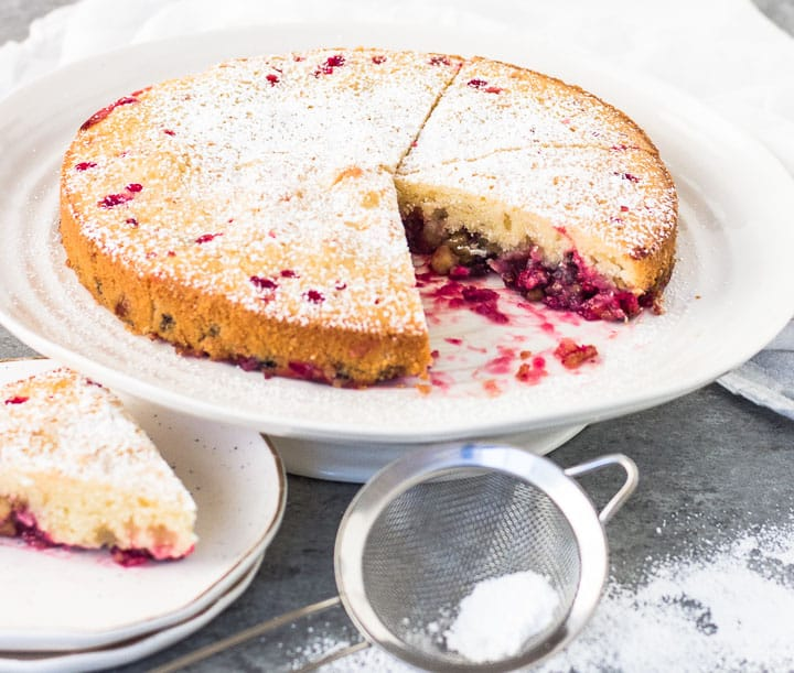 sliced Nantucket cranberry cake on a cake stand with a sifter of powdered sugar in front of it