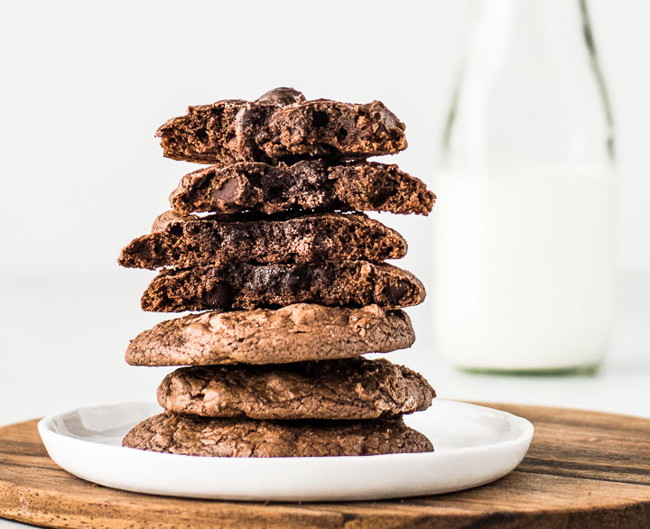 stack of brownie mix cookies on a plate with a jar of milk behind it
