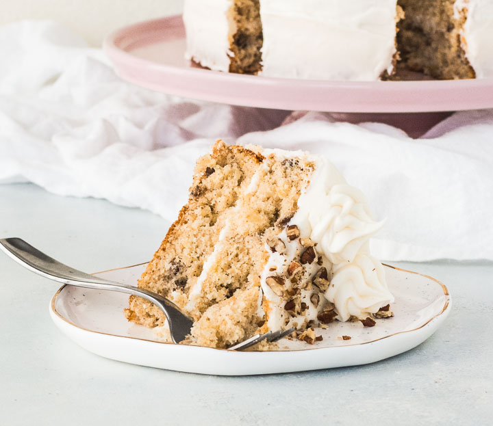 slice of hummingbird cake on a plate in front of a cake stand