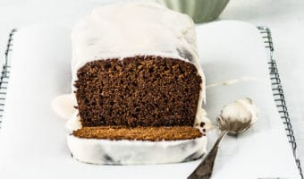 sliced gingerbread loaf on a wire rack with a spoonful of cream cheese glaze next to it