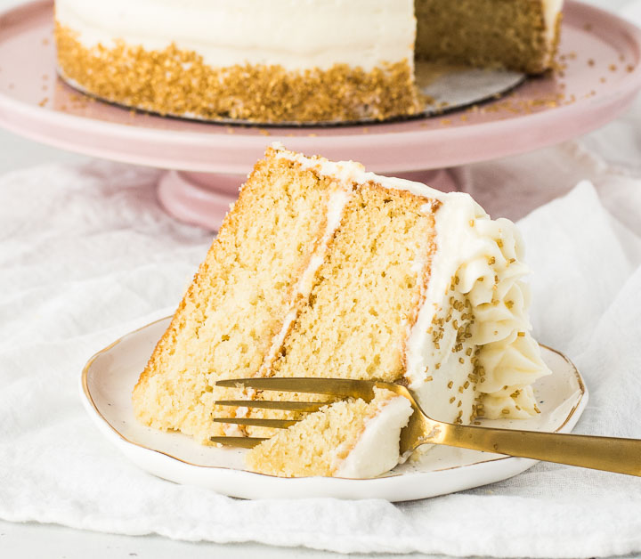 slice of cake on a plate with a fork taking a bite out of it and the rest of the cake in the background