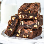 stack of chocolate hazelnut brownies on a plate in front of a jar of milk