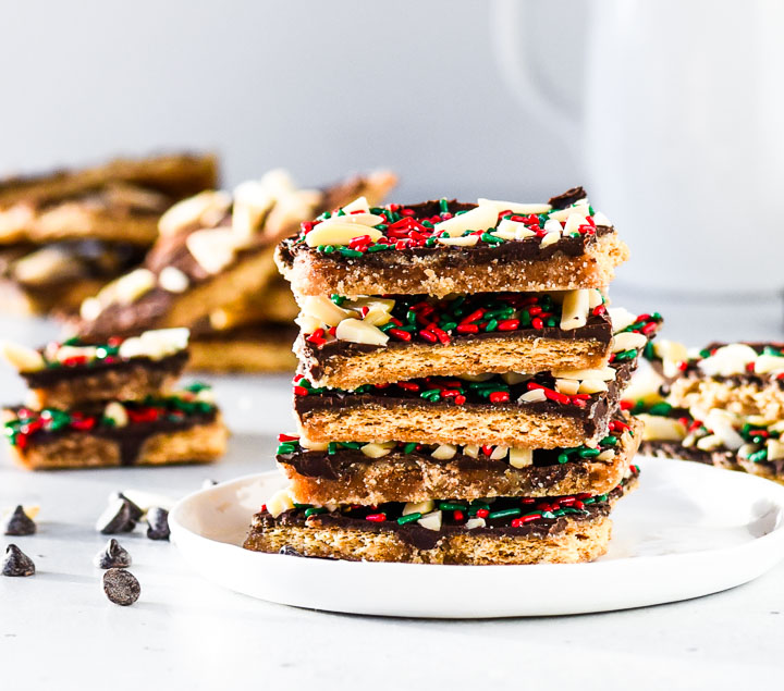 stack of easy graham cracker toffee with red and green sprinkles on a plate with more toffee in the background